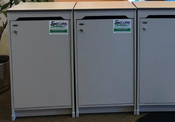 Indianapolis document shredding services image shows 3 Secure Shred containers lined up in a row. They are gray.