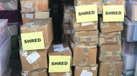 Indianapolis Document Shredding Services image shows a pile of cardboard boxes piled on top of each other. Four of them have a piece of paper on them with the word SHRED.