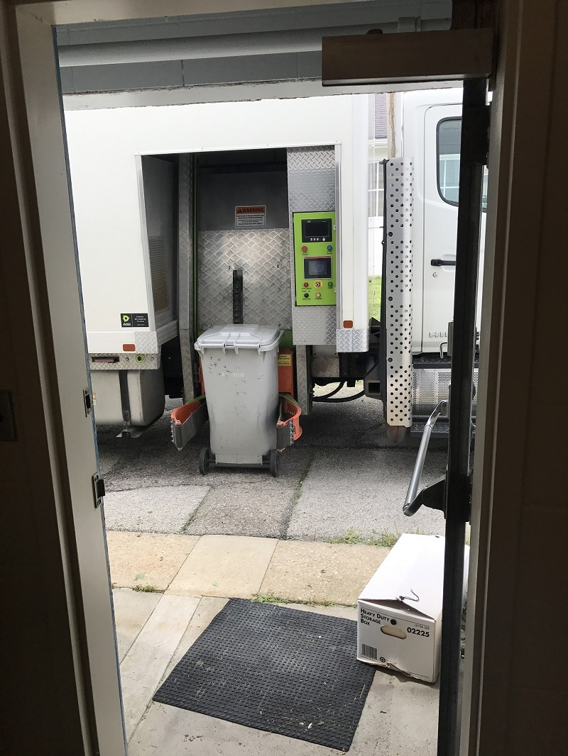 Indianapolis paper shredding company image shows Secure Shred truck outside of building. One of their storage containers is getting ready to be hoisting up to the shredding hopper.