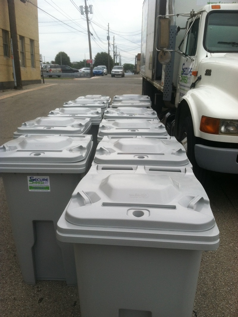 Indianapolis paper shredding company image shows Secure Shred truck in a parking lot. It has 11 of their storage containers beside it.